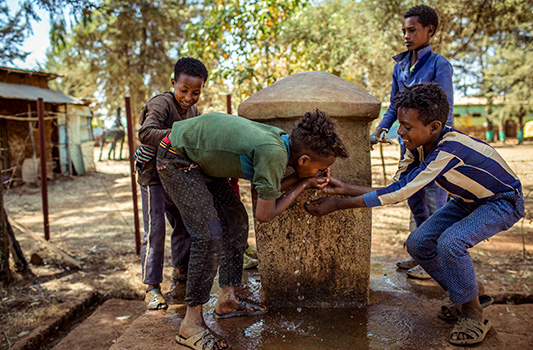 Happy kids drinking water from a fresh water source
