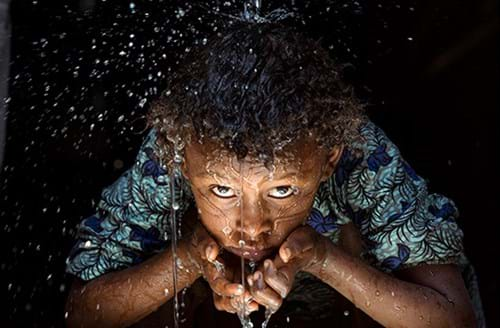 Happy child drinking fresh water