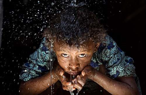 Happy child drinking fresh water