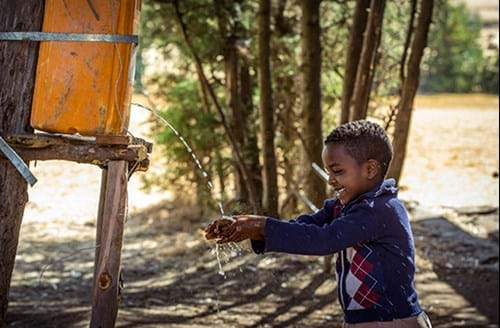 Boy playing in water from fresh water supply
