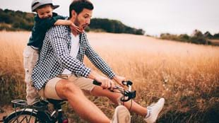 Father and son playing on a bike